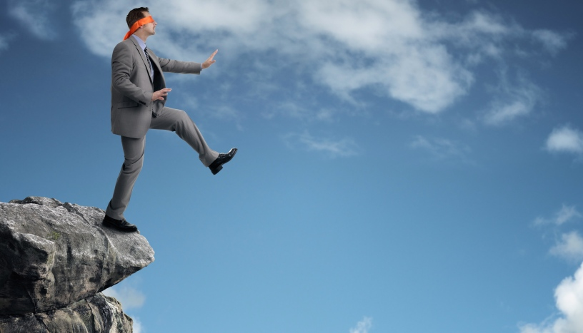 businessman walking off cliff