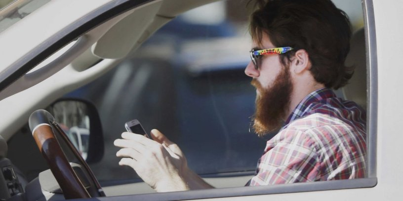 A driver ignores the road as he uses his cellphone behind the wheel.