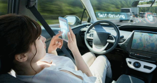 A woman relaxes and reads her phone while her car drives on full automation.