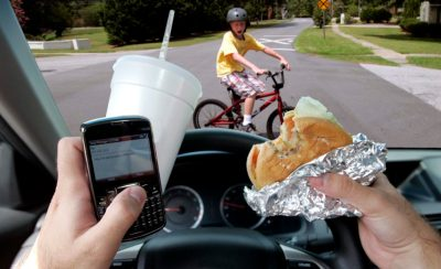 A driver, holding a cellphone, burger and drink in his hands, is bearing down on a child in a bicycle.