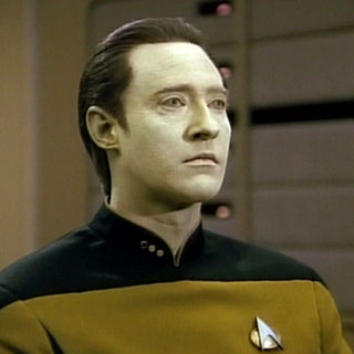 Data, a humanoid android, sits at the ops station aboard the USS Enterprise in Star Trek: The Next Generation.