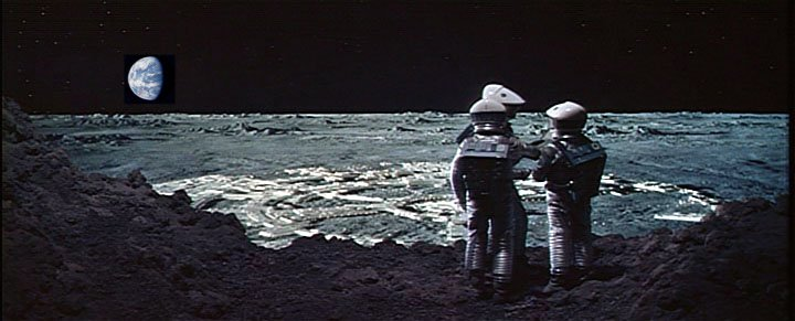 A scene from 2001: A Space Odyssey: Three spacesuited astronauts confer on a lunar hillside overlooking Clavius Base in the background, with Earth on the horizon.