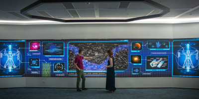 two people consulting a starfield projected on a huge display wall with multiple information displays