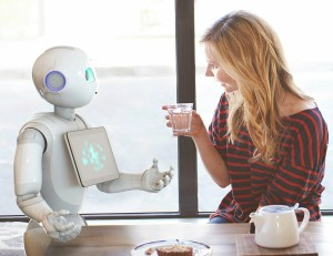 a robot and a woman converse at a table
