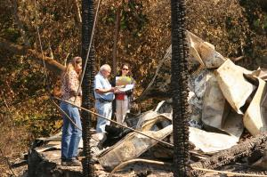 Officials examine the remainsnof a burned-out home after the California wildfires